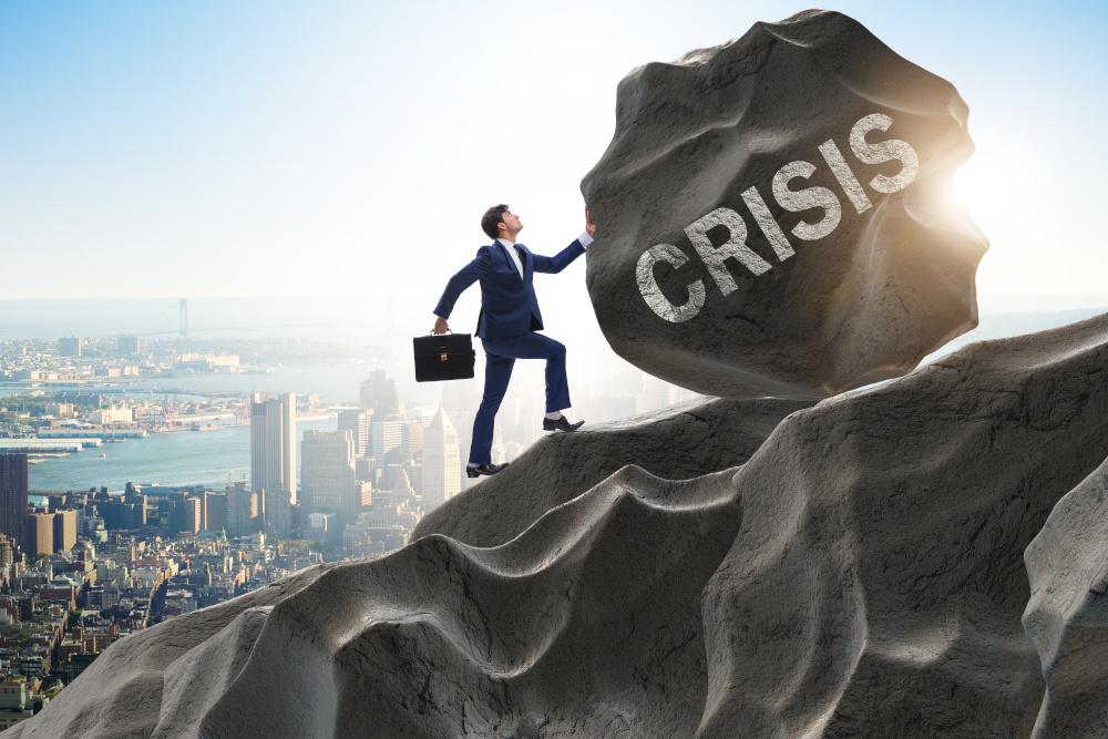 mężczyzna toczący głaz z napisem kryzys po górze