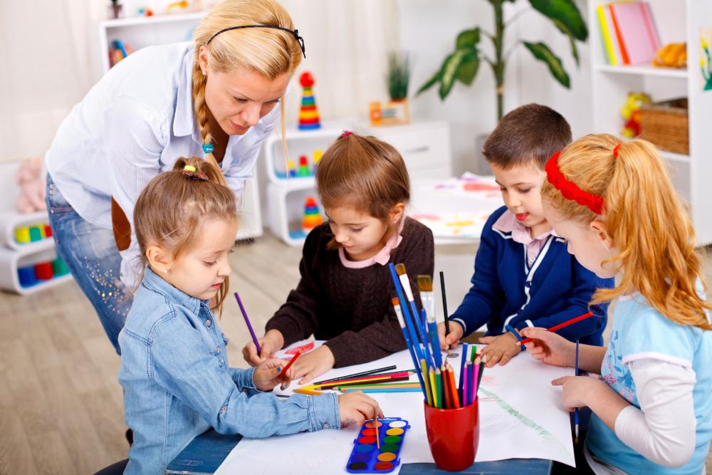 rysujące dzieci w przedszkolu z opiekunką